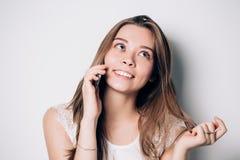 Mujer joven que habla en el teléfono en un fondo blanco Fotos de archivo