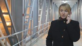 Mujer joven que habla en el teléfono y el paseo en la noche interior Retrato de la muchacha atractiva que habla en el teléfono mó almacen de metraje de vídeo
