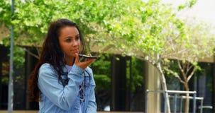 Mujer joven que habla en el tel?fono m?vil en la ciudad 4k metrajes