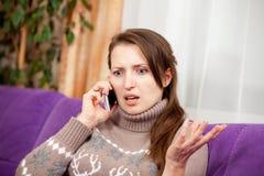Mujer joven que habla en el tel?fono ultrajado foto de archivo libre de regalías
