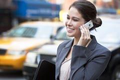 Mujer joven que habla en el teléfono celular en taxi amarillo Imagen de archivo libre de regalías