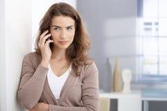 Mujer joven que habla en móvil en sala de estar Fotos de archivo