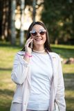 Mujer joven que habla en smartphone al aire libre en un parque Foto de archivo
