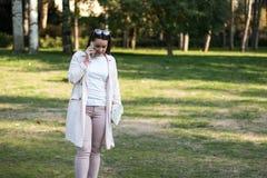 Mujer joven que habla en smartphone en el parque Foto de archivo