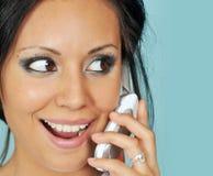 Mujer joven que habla en su teléfono celular Imágenes de archivo libres de regalías