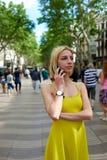 Mujer joven que habla en su teléfono elegante mientras que se coloca en calle de la ciudad con caminar de la gente Foto de archivo libre de regalías