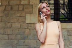 Mujer joven que habla en su teléfono elegante mientras que se coloca en calle de la ciudad con la pared del espacio de la copia Fotografía de archivo libre de regalías
