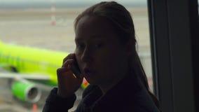 Mujer joven que habla en un teléfono móvil delante de una ventana grande en un aeropuerto almacen de metraje de vídeo