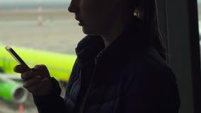 Mujer joven que habla en un teléfono móvil delante de una ventana grande en un aeropuerto almacen de video