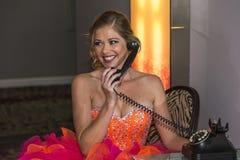 Mujer joven que habla en un teléfono y una sonrisa fotos de archivo