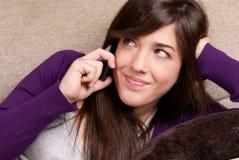 Mujer joven que habla por el primer sonriente del teléfono Imagenes de archivo