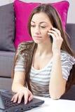 Mujer joven que habla por el teléfono y que usa la computadora portátil Fotos de archivo