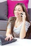 Mujer joven que habla por el teléfono y que usa la computadora portátil Imágenes de archivo libres de regalías