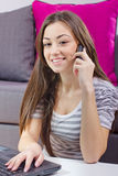 Mujer joven que habla por el teléfono y que usa la computadora portátil Foto de archivo libre de regalías