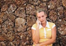 Mujer joven que habla sobre su teléfono móvil Imagen de archivo libre de regalías