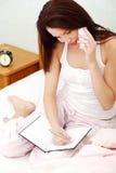 Mujer joven que habla a través del teléfono. Imagen de archivo