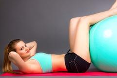 Mujer joven que hace abdominals en el piso con la bola de los pilates Imagen de archivo