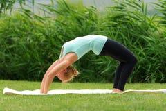 Mujer joven que hace actitud del puente en yoga Foto de archivo libre de regalías