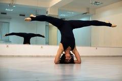 Mujer joven que hace actitud y asana de la yoga del headstand Mujer hermosa que disfruta de yoga dentro en la ropa del deporte, r fotos de archivo libres de regalías