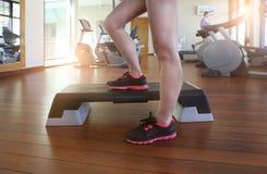 Mujer joven que hace aeróbicos del paso mientras que en club de salud Foto de archivo