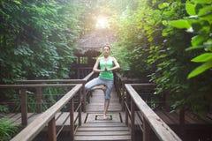 Mujer joven que hace asana de la yoga por la tarde Foto de archivo libre de regalías