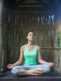 Mujer joven que hace asana de la yoga por la tarde Foto de archivo