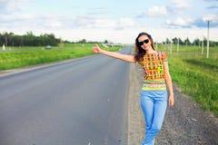Mujer joven que hace autostop Foto de archivo libre de regalías