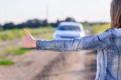 Mujer joven que hace autostop en el campo Imagenes de archivo
