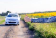 Mujer joven que hace autostop en el campo Imagen de archivo