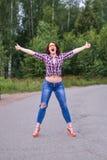 Mujer joven que hace autostop gesto en el campo Fotografía de archivo libre de regalías