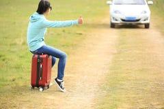 Mujer joven que hace autostop a lo largo de un camino Imagenes de archivo