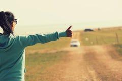 Mujer joven que hace autostop a lo largo de un camino Imagen de archivo libre de regalías