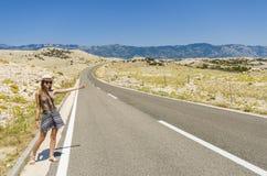 Mujer joven que hace autostop a lo largo del camino vacío Fotografía de archivo libre de regalías