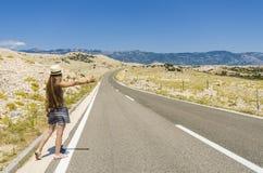 Mujer joven que hace autostop a lo largo del camino vacío Fotografía de archivo