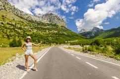 Mujer joven que hace autostop a lo largo del camino vacío Foto de archivo libre de regalías