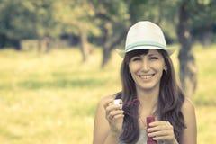 Mujer joven que hace burbujas de jabón en parque del verano Imagen de archivo