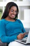 Mujer joven que hace compras en línea Imagen de archivo libre de regalías