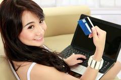 Mujer joven que hace compras en línea Fotografía de archivo
