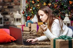Mujer joven que hace compras en línea con la tarjeta de crédito y el ordenador portátil en casa Concepto de las compras de la Nav Foto de archivo
