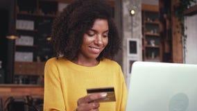 Mujer joven que hace compras en línea en el ordenador portátil con la tarjeta de crédito almacen de video