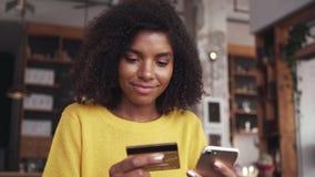 Mujer joven que hace compras en línea en el teléfono móvil con la tarjeta de crédito metrajes
