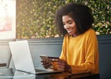 Mujer joven que hace compras en línea en el teléfono móvil con la tarjeta de crédito imagen de archivo libre de regalías