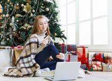 Mujer joven que hace compras en línea en interior acogedor de la Navidad Imágenes de archivo libres de regalías