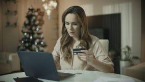 Mujer joven que hace compras en l?nea en el tiempo de la Navidad Compras en l?nea de la Navidad metrajes