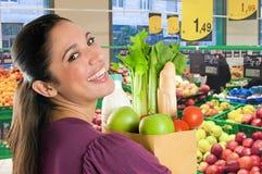 Mujer joven que hace compras en un supermercado Imagen de archivo libre de regalías