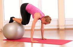 Mujer joven que hace ejercicio de la aptitud con la bola del ajuste. Foto de archivo