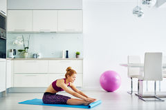 Mujer joven que hace ejercicio de la aptitud en casa imagen de archivo libre de regalías