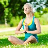 Mujer joven que hace ejercicio de la yoga Imagen de archivo