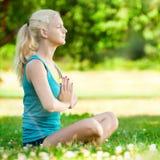 Mujer joven que hace ejercicio de la yoga Imagen de archivo libre de regalías