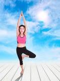 Mujer joven que hace ejercicio de la yoga en el piso de madera Imagen de archivo libre de regalías
